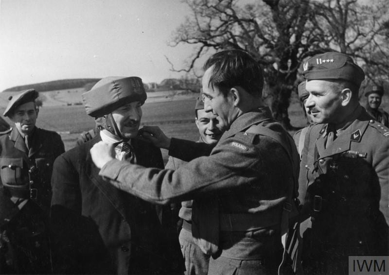 THE POLISH ARMY IN BRITAIN, 1940-1947 (HU 128274) Second Lieutenant of the 1st Polish Independent Parachute Brigade adjusting a bungee helmet (paratrooper's training helmet) on Clement Attlee's head during his visit to the Brigade. Cupar, 20 April 1942. Colonel Stanislaw Sosabowski, the Commander of the Brigade, is on the right. Copyright: © IWM. Original Source: http://www.iwm.org.uk/collections/item/object/205402362